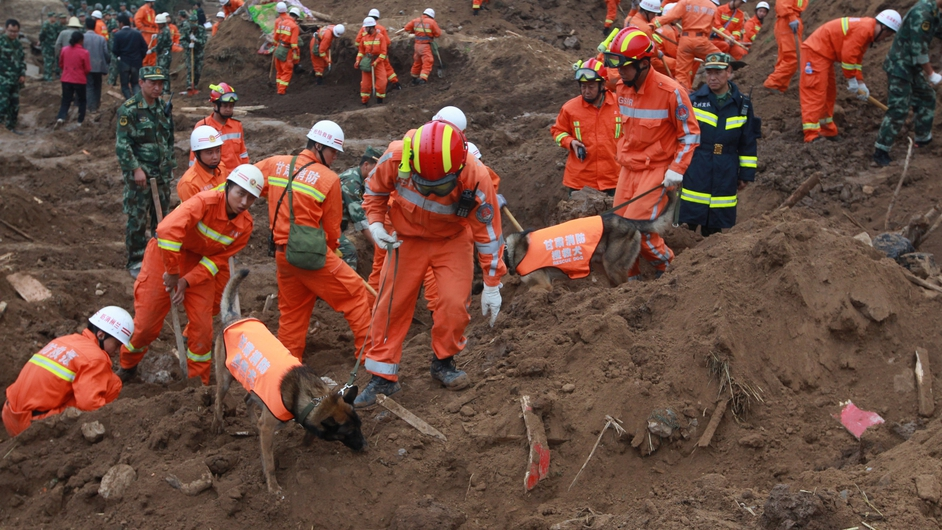 Rescue workers search for buried people in the aftermath of an earthquake in Gansu province in northwest China