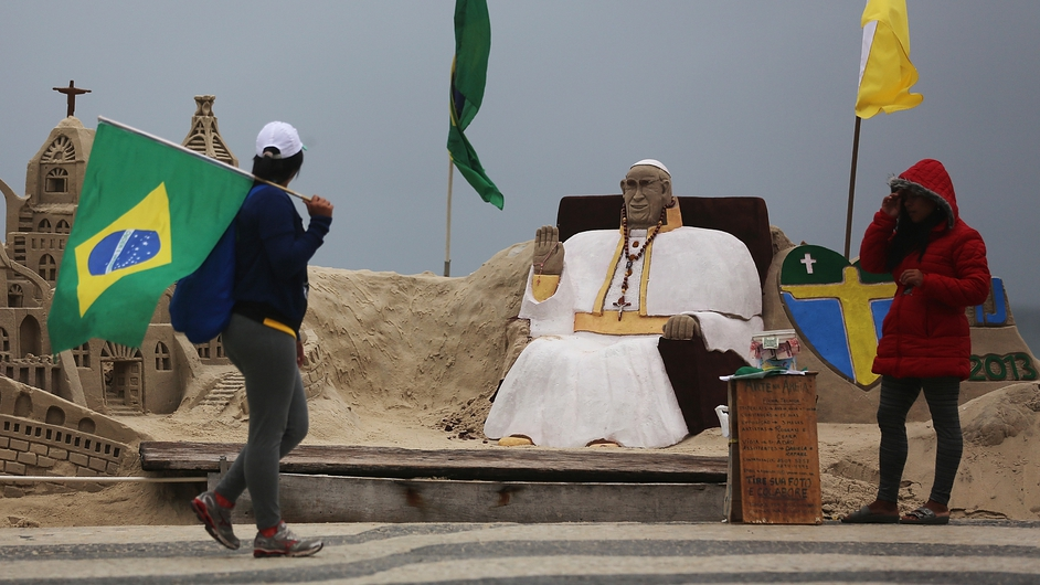 A woman walks past a sand sculpture of Pope Francis on Copacabana Beach as part of World Youth Day celebrations