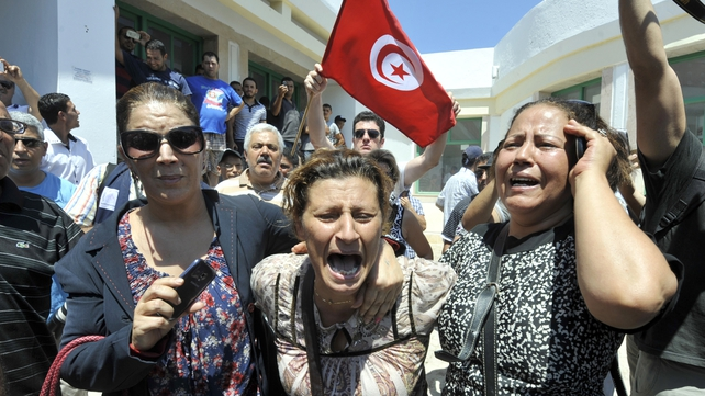 Tunisians react outside a hospital after the killing of Mohamed Brahmi