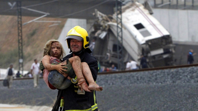 A firefighter carries an injured young girl away from the scene of the crash