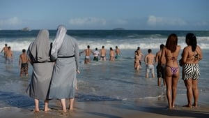 Two Polish nuns look on as youths enjoy the good weather