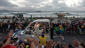 Pope Francis waves from the popemobile as he arrives at Copacabana beach to participate in a re-enactment of the Stations of the Cross