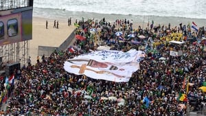 A huge banner with an image of Pope Francis is spread out at Copacabana beach