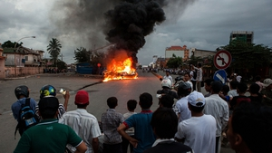 Protesters watch a burning police car in the Cambodian capital of Phnom Penh