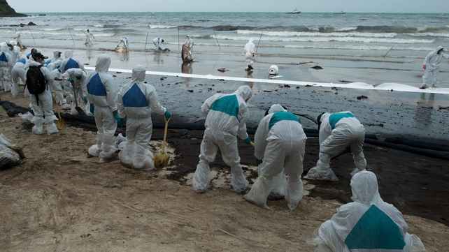Soldiers and volunteers work to clear sludge off the white sand beach in Koh Samet