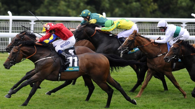 Ryan Moore riding Garswood (red) en route to victory at Glorious Goodwood