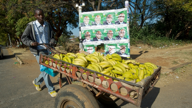 A man passes elections posters on his way to work in Harare
