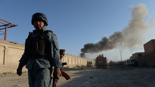 An Afghan policeman stands guard beside the site of a bomb attack in Kabul
