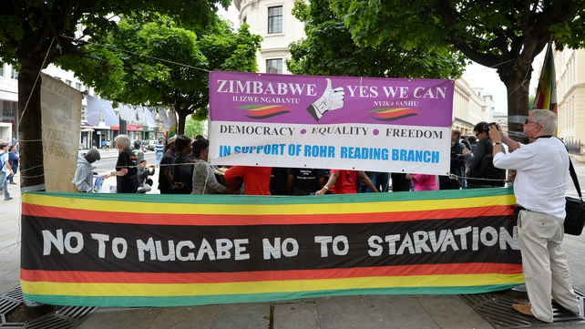 Anti-Mugabe protesters gather outside the Zimbabwean Embassy in London