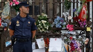 A policeman stands guard beside a memorial to the train crash victims in Santiago de Compostela