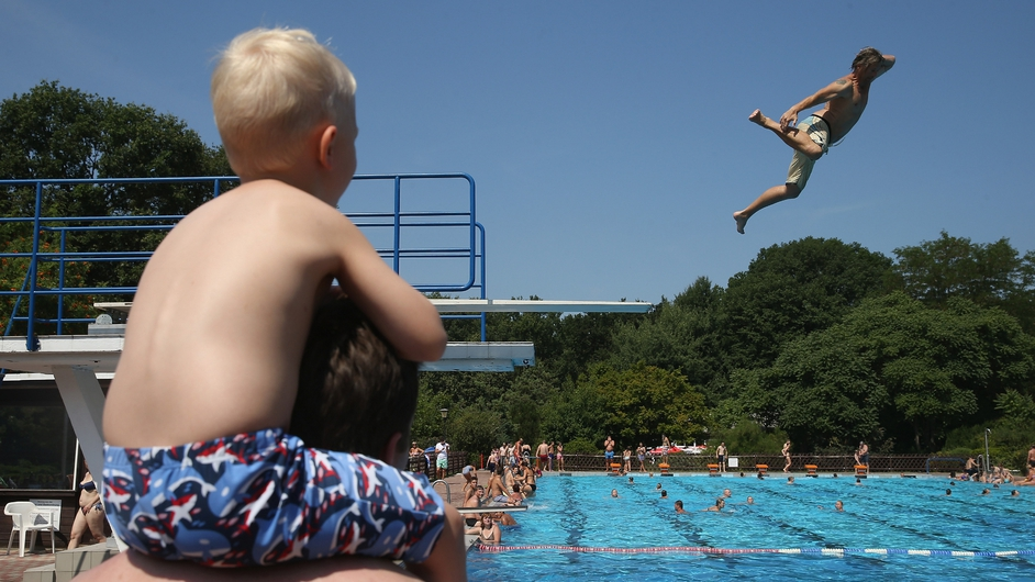 A young boy watches a diver attempt to cool off in Berlin, Germany