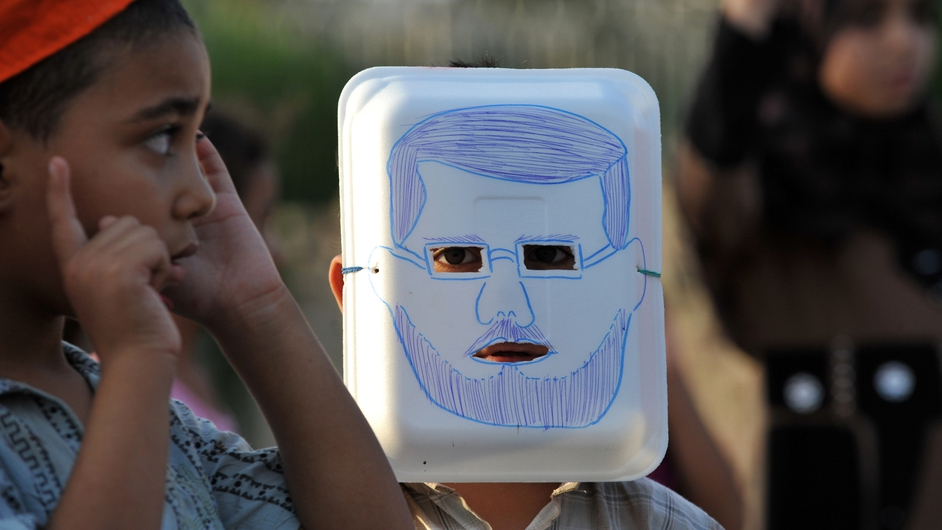 A young supporter of ousted president Mohammed Moursi wears a mask depicting the leader during a children's march in Egypt