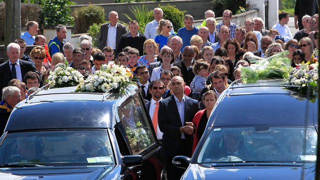 Eoghan and Ruairi's mother Kathleen (C) walks behind her sons' coffins