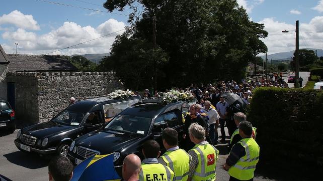 Mourners walk behind the cortege in Ballinkillen