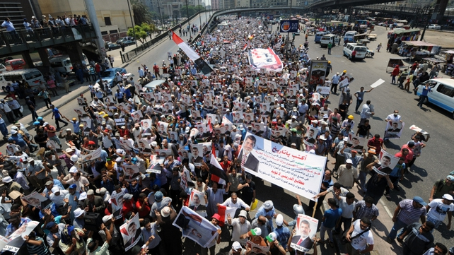 Pro-Mursi supporters carry posters bearing his portrait during a demonstration against the government in Cairo