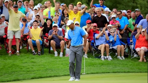 Tiger Woods makes a birdie putt on the 12th