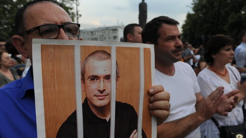 A demonstrator holds up a portrait of Mikhail Khodorkovsky during a rally marking his 50th birthday last June