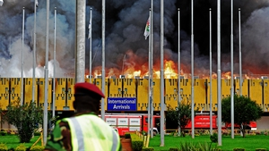 A soldier looks on as fire rages through a terminal at Jomo Kenyatta international airport in Nairobi, Kenya
