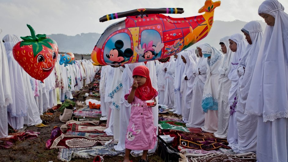 A young girl eats ice cream as Indonesian muslims perform Eid al-Fitr prayers to mark the end of Ramadan