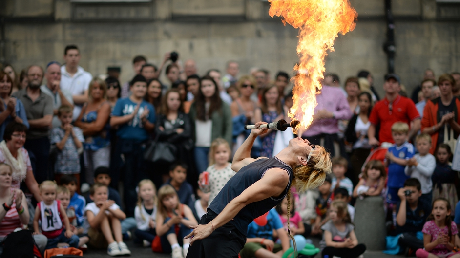 A fire-breather performs on the street at the Edinburgh Fringe Festival