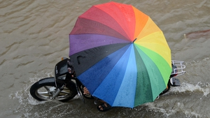 An Indian commuter attempts to dodge the showers during monsoon season