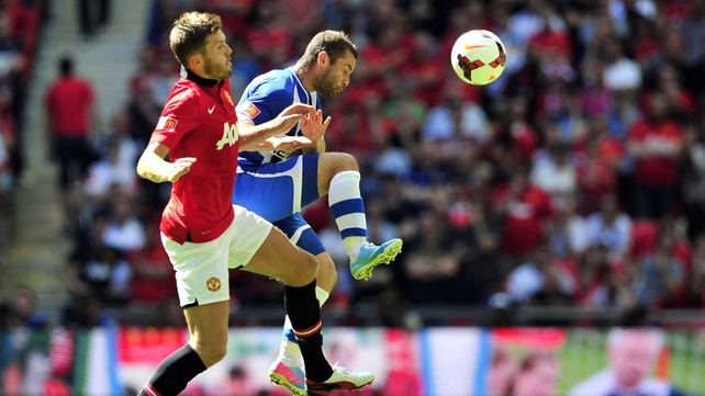Manchester United's English midfielder Michael Carrick (L) vies with Wigan Athletic's Malaysian-born Scottish midfielder Shaun Maloney