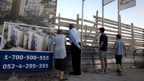 Israelis stand next to a sales promotion sign for a new Jewish neighbourhood in east Jerusalem