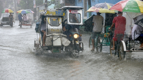 Residents commute along a flooded stretch of road during heavy rain in the suburbs of Manila