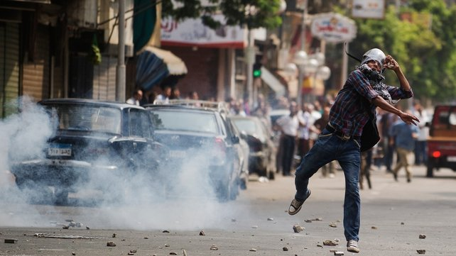A protester throws a stone in Cairo as police fire tear gas