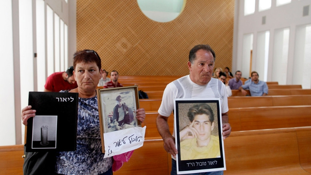 Yaakov (R) and Miriam, parents of Lior Tobul, who was killed by Palestinian militants in 1990, hold up pictures of him before a court hearing to protest the government's decision to release Palestinian prisoners