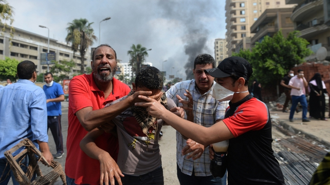 A pro-Mursi supporter affected by tear gas is helped away as police move in