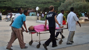 Hospital staff and a colleague help a wounded MSF foreign aid worker after a Somali gunman opened fire on an MSF compound