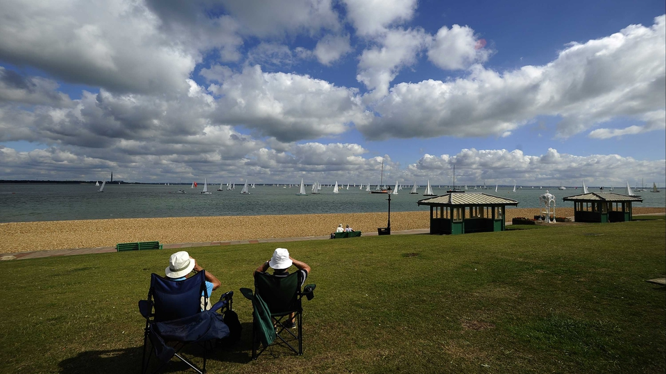 Spectators watch the action from The Green at the Aberdeen Asset Management Cowes Week in Cowes, Isle of Wight