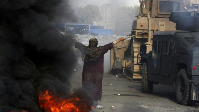 A woman tries to stop forces from entering a camp in Cairo