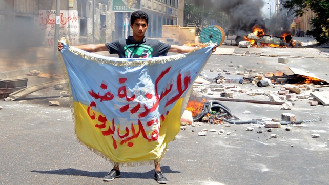 A Muslim Brotherhood supporter holds a banner reading in Arabic: 'Alexandria is against the coup'