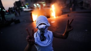 A young boy flashes the victory sign at the funeral of a 10-year-old boy in Bahrain