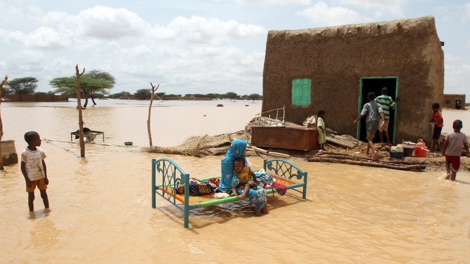 A Sudanese woman sits outside her home as floods hit the capital of Khartoum