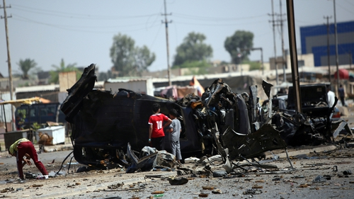 The scene of a car bomb in Baghdad's eastern neighbourhood of Baladiyat is inspected