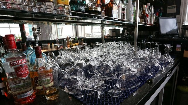Broken glasses litter the counter of a bar in Wellington after the quake