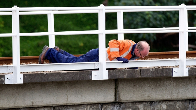 An engineer carries out a spot check for structural damage on a railway bridge