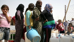 Syrian refugees queue for water at the Domiz refugee camp in northern Iraq