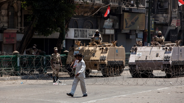 Egyptian military armoured vehicles stand guard at a checkpoint on the edge of Tahrir Square