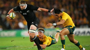 Kieran Read of the All Blacks breaks the tackle of Michael Hooper and Christian Lealiifano of the Wallabies