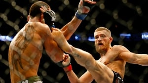 Conor McGregor kicks Max Holloway in their UFC bout in Boston, Massachusetts