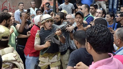 A soldier tries to control crowd while escorting a man out of Al-Fateh mosque in Cairo