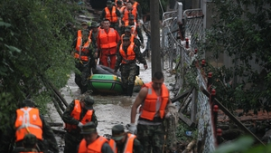 Rescuers searching for victims in a flooded area in Hongshi township of Huadian, northeast China
