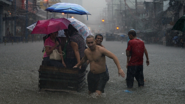 People struggle to carry their belongings out of flood-damaged areas
