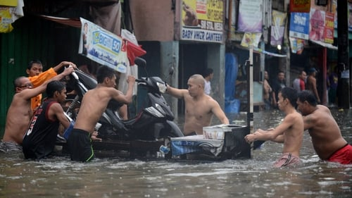 At least seven people were killed as monsoon rains triggered floods and landslides in Manila