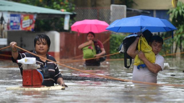Residents in Manila wade through waist-deep water