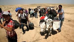 Syrian refugees cross the border into the northern Iraqi region of Kurdistan
